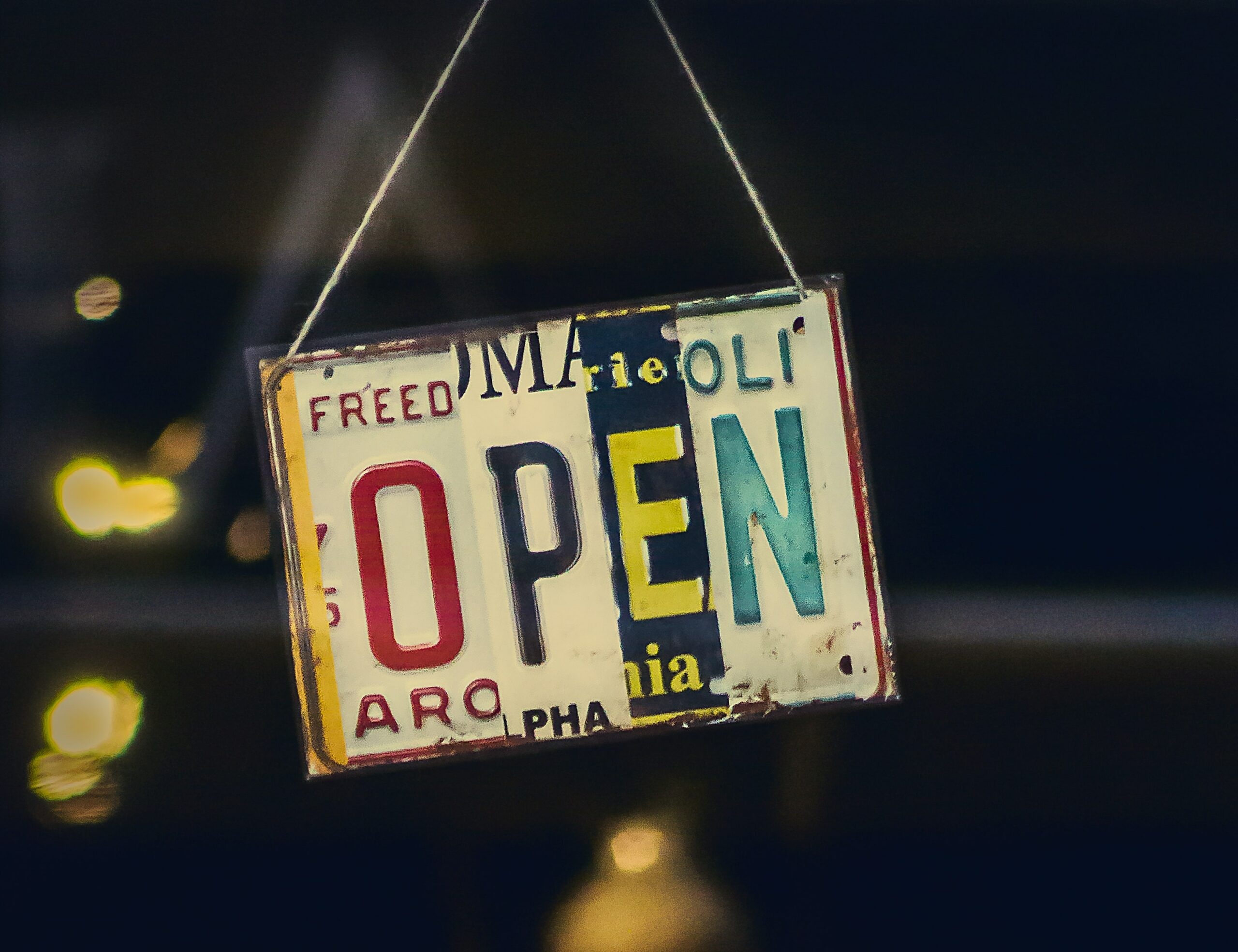 A hanging sign says 'open' in different alphabets
